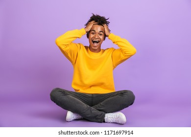 Portrait of joyous african american boy screaming and grabbing head while sitting on floor with legs crossed isolated over violet background