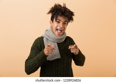 Portrait of joyous african american guy wearing sweater and scarf gesturing at camera isolated over beige background