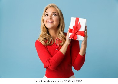 Portrait of joyous blond woman 20s wearing red shirt holding gift box isolated over blue background in studio