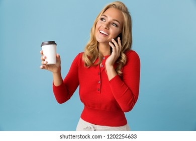 Portrait of joyous blond woman 20s holding takeaway coffee while speaking on mobile phone isolated over blue background in studio