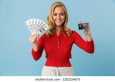 Portrait of joyous blond woman 20s wearing red shirt holding fan of dollar money and credit card isolated over blue background in studio