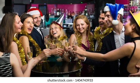 Portrait of joyous females and males in caps and garlands in the night club