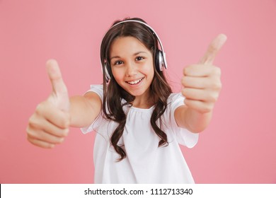 Portrait of joyous girl 8-10 in casual clothing showing thumbs up at camera with both hands while listening to music via wireless headphones isolated over pink background