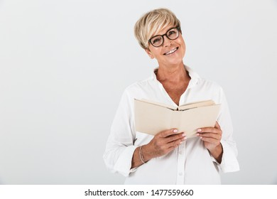 Portrait of joyous middle-aged woman wearing eyeglasses reading book isolated over white background in studio