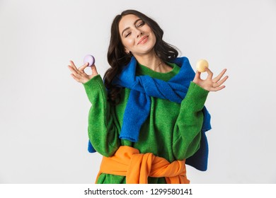 Portrait of joyous woman 30s in colorful clothes holding macaron cookies while standing isolated over white background