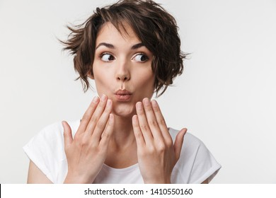 Portrait of joyous woman with short brown hair in basic t-shirt covering her mouth with hands isolated over white background