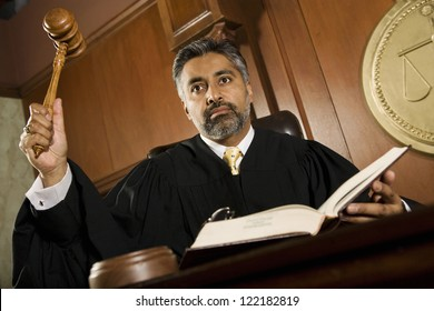 Portrait of judge pounding mallet in courtroom