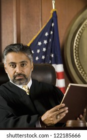 Portrait of judge sitting with book in courtroom