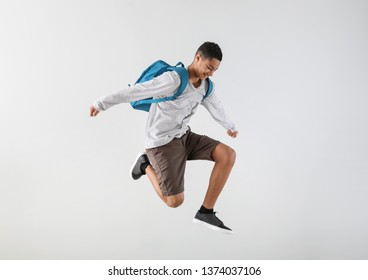 Portrait of jumping African-American teenage boy on grey background
