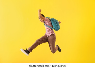 Portrait of jumping African-American teenage boy on color background - Shutterstock ID 1384838423
