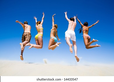 Portrait of jumping young people a backs on the beach
