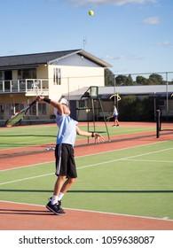 Portrait of Junior Boy Teenage Children Tennis Player Serving Ball Whilst Playing Match on Court in Summer Weather