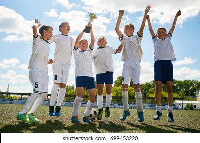 Portrait of junior football team cheering happily and jumping holding champions cup after winning match
