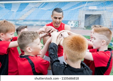 Portrait of junior football team stacking hands during motivational pep talk before match in outdoor stadium, focus on young coach, copy space