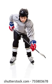 Portrait of junior ice hockey player on the alert with full equipment and uniform posing for a shot with a puck. Isolated on white background.