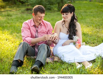 Portrait of just married couple changing rings on meadow
