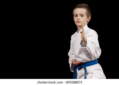 Portrait of a karate kid  in kimono ready to fight isolated on black background.