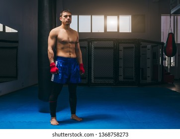 Portrait of kickbox professional fighter with naked muscular torso posing for a camera. Sportsman dressed in blue boxing shorts and having thir fists wrapped in red bandages. Sport concept. Dark gym