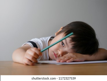 Portrait Kid boy holding colour pencil sitting alone and looking out with bored face,Preschool child laying head down on table with sad face,Five years old kid bored with school homework,spoiled child