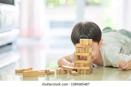 Portrait of kid cute asian boy playing a blocks wood game. selective focus. Copy space.