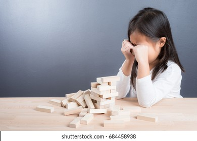Portrait of kid cute asian girl age 6 year  sad to broken down blocks wood game on wooden table background. With copy space for text .