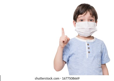 Portrait of kid with face mask pointing finger up, isolated on white background