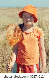 Portrait of kid girl with butterfly net over rural landscape