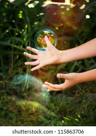 Portrait of kid hands going to catch the bubble