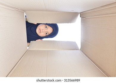 portrait of a kid looking for something inside box