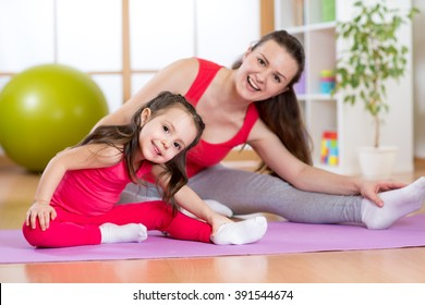 Portrait of kid and mother doing physical exercise at home
