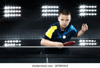Portrait Of Kid Playing Tennis On Black Background