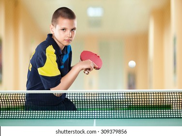 Portrait Of Kid with Racket Playing table Tennis in Action shot