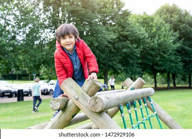 Portrait kid sitting on wooden climbing frame in the park, Child enjoying activity in a climbing adventure park on summer sunny day, Cute little boy having fun on a playground outdoors.