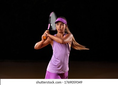 Portrait of kid - tennis player. Beautiful girl athlete with racket in pink sporswear and hat on tennis court. Fashion and sport concept.
