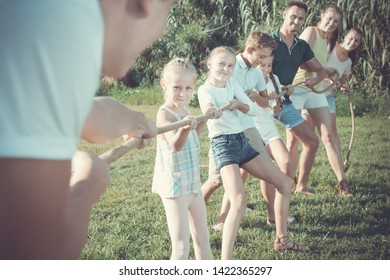 portrait of kids with parents playing active games in summer park, tugging war
