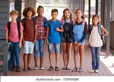 Portrait of kids standing in elementary school hallway