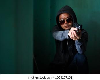 Portrait killer man with gun shooting in poor light, Gunman, Bodyguard. Unofficial police.