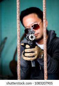 Portrait killer man with gun shooting in poor light, Gunman.