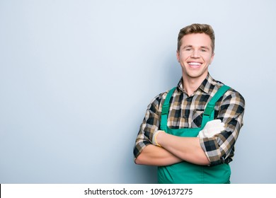 Portrait of kind cheerful excited smart professional friendly expert handsome with beaming shiny smile handyman wearing green overalls standing with folded hands isolated on gray background copyspace