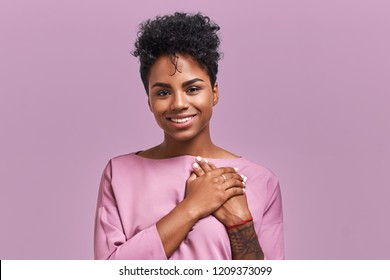 Portrait of kind hearted African American female in fashionable overalls, keeps hands on chest, shows her kindness and sympathy, has pleased cheerful expression, isolated over lavender background