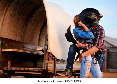 Portrait of kissing a guy and girl in cowboy hats