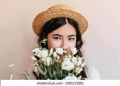 Portrait of korean lady holding flowers and looking at camera. Studio shot of asian girl in straw hat with white eustomas.