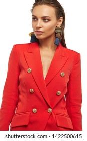 Portrait of lady with tanned skin, wearing red blazer and long dangle earrings, adorned with massive metal pendants and navy blue tassels. The young woman with slicked down hair is looking to side.