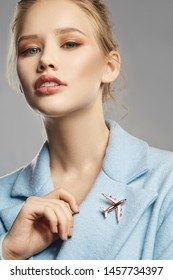 Portrait of lady with tied back fair hair, wearing sky blue coat with massive brooch in view of silver airplane on lapel. The woman is raising head and touching her collar on the gray background.