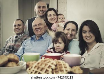 Portrait of large happy multigeneration family having tea at home