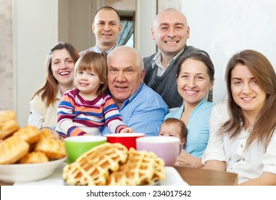 Portrait of large happy three generations family sits on sofa at home together