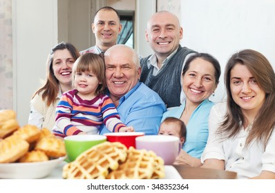 Portrait of large joyful three generations family sits on sofa in home interior