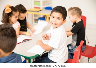 Portrait of a Latin preschool pupil working on a writing assigment and enjoying school