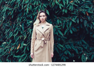 Portrait of latina caucasian multi cultural woman posing near a wall with a green grapes leaves outside in autumn. Blonde brunette woman in beige coat, still standing model, en face photo