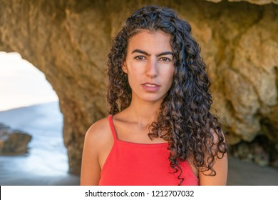 Portrait of latino woman with curly hair, red top and denim shor